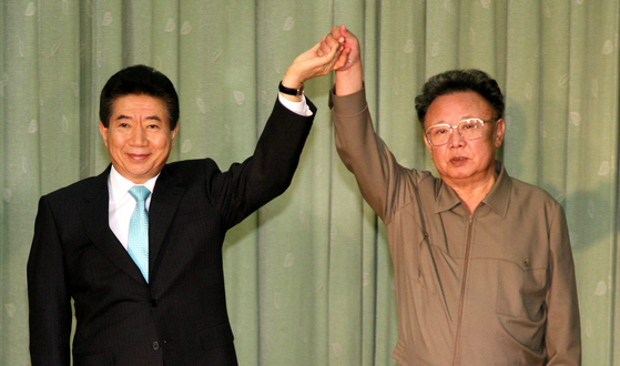 Former South Korean President Roh Moo-hyun, left, holds hands with former North Korean leader Kim Jong-il in 2007 during their summit in Pyongyang. [YONHAP]