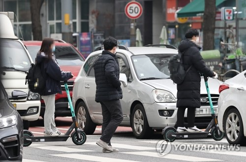 People ride electric scooters across a street near Hoegi Station in eastern Seoul on Thursday. A revised law that enables people to ride electric scooters in bike lanes went into effect that day. Under the revised law, people aged 13 or older can ride on scooters without a driver's license; however, from April next year, all electric scooters will require a motorcycle license and only those aged 16 or older will be eligible to obtain one. [YONHAP]