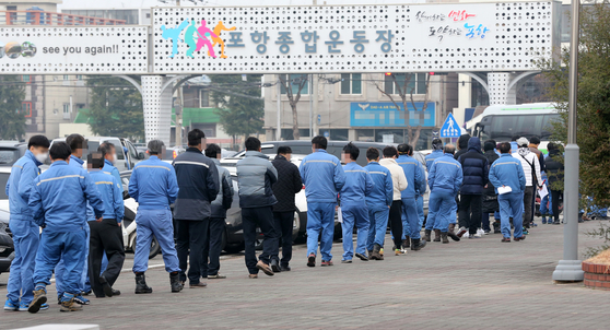 Workers at the Pohang Iron and Steel Industrial Complex form a long queue on Friday at the Pohang Stadium in Pohang, North Gyeongsang, to take Covid-19 tests. Since Thursday, the city has administered tests to 3,400 workers who recently had trips outside the city or who displayed symptoms. [YONHAP]