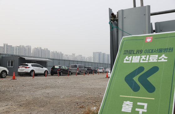 Cars wait in line at a drive-through Covid-19 testing site Friday in Gangseo District, western Seoul. [YONHAP]