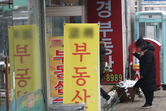 A passerby looks at real estate prices at a real estate agency in Seongbuk District, northern Seoul. House prices in northern Seoul increased in November, according to data from KB Kookmin Bank on Sunday. Of the 25 districts in Seoul, the apartment growth rate was highest in Nowon District, followed by Seongbuk District and Gangbuk District, all in northern Seoul. [YONHAP]