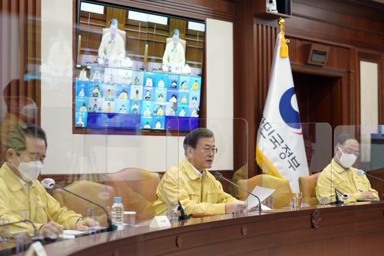 El presidente Moon Jae-in habla en una reunión de emergencia de la Sede Central de Contramedidas de Seguridad y Desastres en Seúl el domingo para discutir la respuesta al coronavirus cuando Corea superó la marca de 1,000 casos el día anterior.  El encuentro contó con la participación de jefes de agencias gubernamentales, mientras que los jefes de gobiernos municipales y provinciales participaron virtualmente.  [YONHAP]