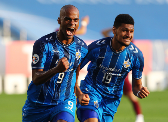 Junior Negao, left, celebrates with Bjorn Johnsen after scoring the winning goal for Ulsan Hyundai FC against Vissel Kobe in the AFC Champions League semifinal in Qatar on Sunday. [REUTERS/YONHAP]