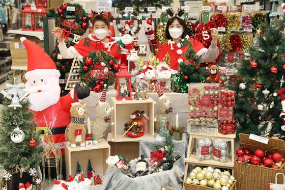 Models pose beside Christmas ornaments and decorations at supermarket chain Emart's Yongsan branch in central Seoul, Monday. The discount chain is offering Christmas trees, lights and other seasonal decorations at discount prices up to 60 percent off from Dec. 17 through 25. [EMART]