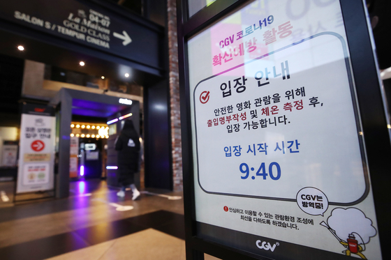 A sign posted in front of a movie theater which requires audiences to check in using a smart attendance system and to measure their temperatures. [YONHAP]