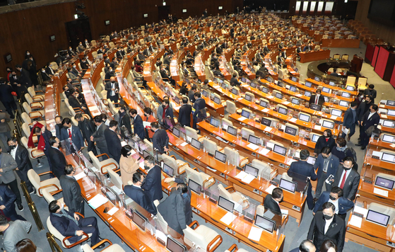 Opposition People Power Party lawmakers shuffle out of the National Assembly's plenary chamber in protest over the ruling Democratic Party's ending of its filibuster over a controversial anti-leaflet bill. The DP passed the bill with its overwhelming majority Monday evening. [YONHAP]