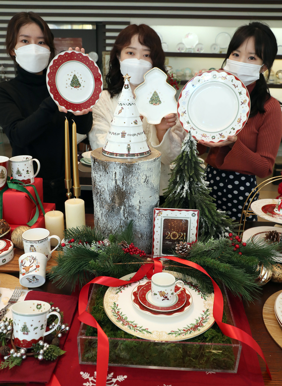 Models pose with various Christmas-themed dishes at a Hankook Chinaware store in Dongdaemun District, central Seoul on Tuesday. This year's Christmas-themed package includes dishes, mugs, photo frames and candlesticks. [YONHAP]