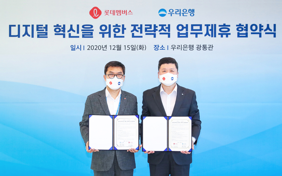 Woori Bank CEO Kwon Kwang-seok, right, and Jeon Hyung-shik, CEO of Lotte Members, pose for a photo after inking a digital strategy partnership Tuesday at Woori Bank's main branch in Jung District, central Seoul. [WOORI BANK]