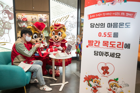 The Charlotte volunteers, a group of Lotte employees, make scarves for children from lower-income households at Lotte World in Songpa District, southern Seoul, on Wednesday. The profit from sales of knitting kits will be used to help with heating costs for the households, and the scarves will be donated to the children via the Salvation Army. [LOTTE WORLD]