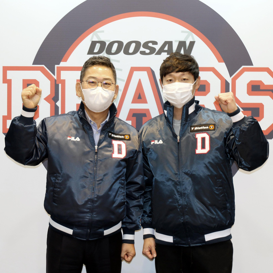 Doosan Bears' outfielder Jung Soo-bin, right, poses for a photo after signing his free agent contract on Wednesday. [YONHAP]