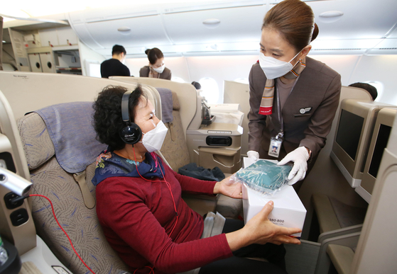An Asiana Airlines flight attendant hands out a souvenir to a passenger who flew on Oct. 24 on the airline's A380. [NEWS1]