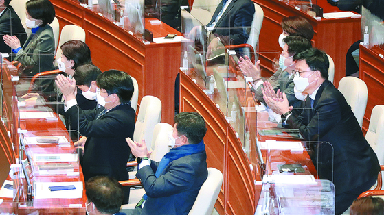 Ruling Democratic Party lawmakers applaud the passage of the controversial revision to the Act on the Corruption Investigation Office for High-ranking Officials in the National Assembly last Friday.  [OH JONG-TAEK]