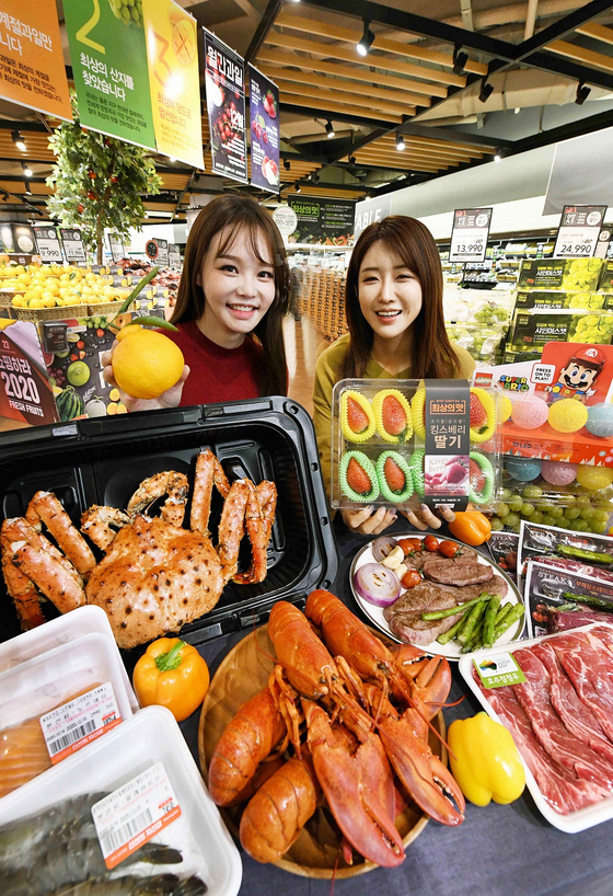 Models pose with groceries that will be discounted at Homeplus's offline and online channels for two weeks from Dec. 30 for those who choose to host year-end parties at home. [YONHAP]