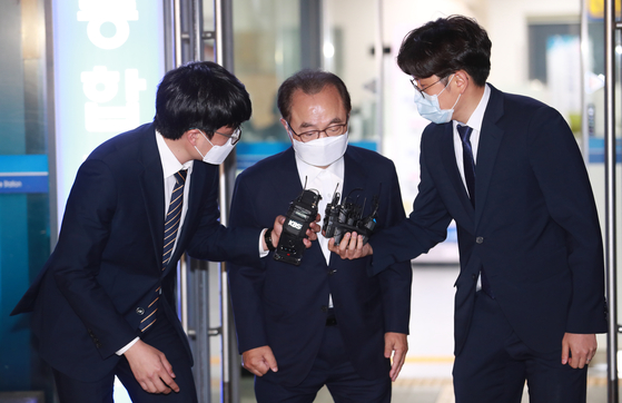 Former Busan Mayor Oh Keo-don, center, is questioned by reporters as he steps out of the Busan District Court in June, after a warrant filed for his arrest was denied by the court. [YONHAP]