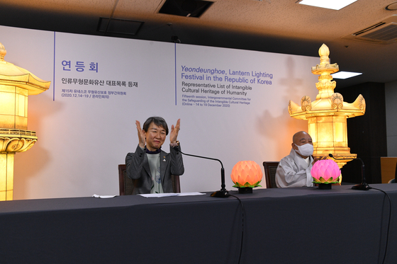 Chung Jae-suk, left, applauds the announcement by Unesco's 15th session of the Intergovernmental Committee for the Safeguarding of the Intangible Cultural Heritage of the inscription of Korea's Yeondeunghoe on the Representative List of Intangible Cultural Heritage of Humanity on Wednesday evening at the National Palace Museum of Korea, central Seoul. She is joined by Buddhist monk Wonhaeng, president of the Jogye Order of Korean Buddhism, right. [CULTURAL HERITAGE ADMINISTRATION]