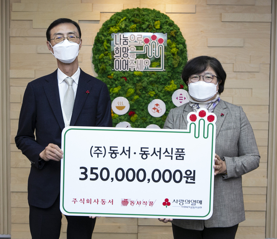 Choi Sang-in, associate vice president of Dongsuh Foods, left, and Kim Youn-soon, secretary general of Community Chest of Korea, during the donation event held in central Seoul on Thursday. [DONGSUH]