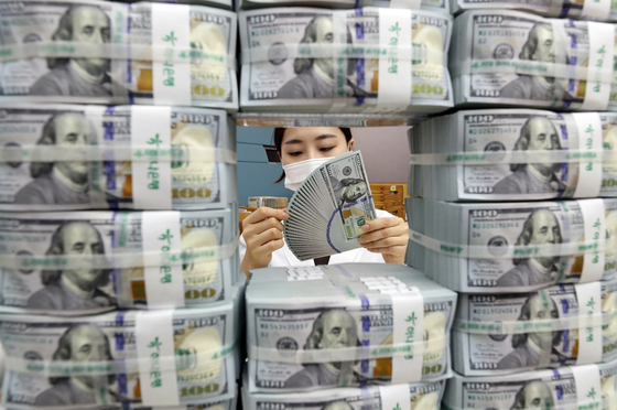 A staffer organizes U.S. dollars at KEB Hana Bank's main branch in Jung District, central Seoul, earlier this month. [YONHAP]