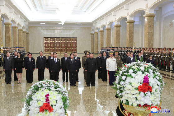 North Korean leader Kim Jong-un, third from left in front row, and his top cadre, including his younger sister Kim Yo-jong, second from left, on Thursday pay tribute to their father and former leader Kim Jong-il on the ninth anniversary of his death, as shown in a photograph from state media. The ceremony took place at the Kumsusan Palace of the Sun, where Kim Jong-il and his father Kim Il Sung's bodies are laid in state. [YONHAP]
