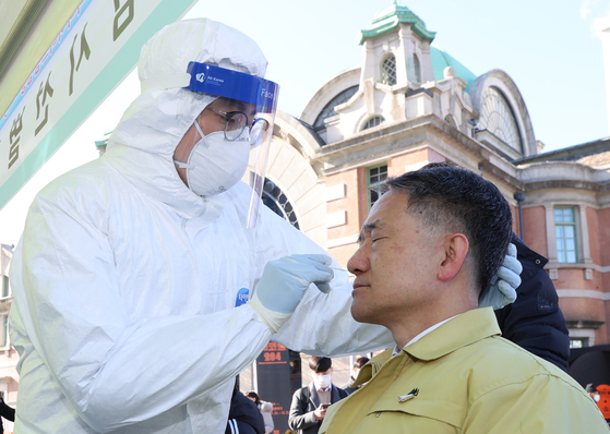 Health Minister Park Neung-hoo receives a rapid antigen test for the coronavirus Wednesday at a Covid-19 testing site at Seoul Station Square in central Seoul. The results turned out negative. The Korean government had until recently refused to use the test on the public, citing possible faulty outcomes. People who test positive on the test must take a follow-up, more accurate PCR test to be diagnosed with the virus. [NEWS1]