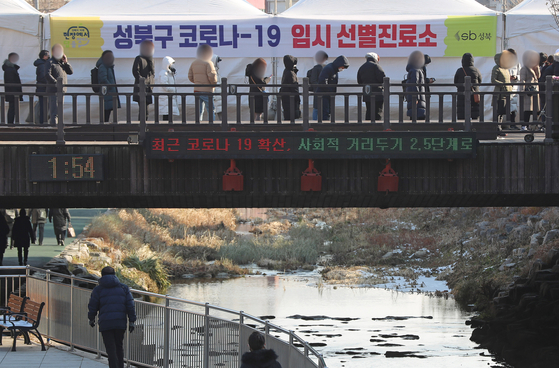 People wait to get tested at a Covid-19 testing site in Seongbuk District, northern Seoul, Friday. [YONHAP]