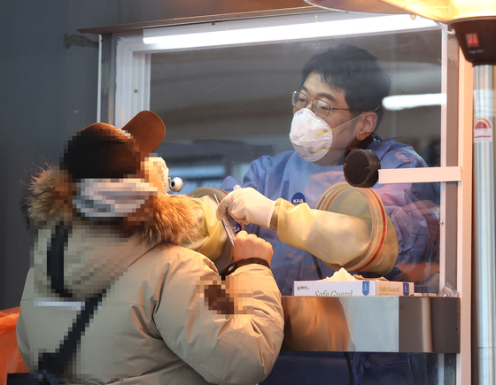 A frontline medical worker administers a coronavirus test at a Covid-19 testing site in Jung District, central Seoul, Saturday. [YONHAP]