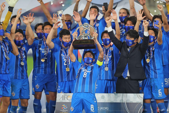 Ulsan Hyundai FC midfielder Sin Jin-Ho lifts the winners' trophy after the Asian Football Confederation Champions League finals match between Iran's Persepolis FC and Korea's Ulsan on Saturday in Qatar. [AFP/YONHAP]