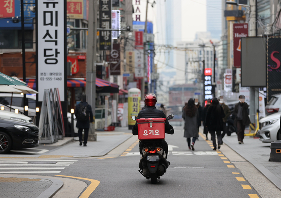 A Yogiyo delivery worker delivering lunch in Gangnam District, southern Seoul, on Dec. 10. Delivery workers have increased as more people are placing orders via food delivery platforms such as Yogiyo or Baemin. Yet their job security has remained unstable, prompting the government to take action in improving platform worker's rights. [YONHAP]