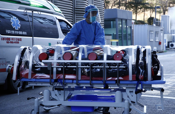 A Covid-19 patient arrives at the National Health Insurance Ilsan Hospital on Sunday after the hospital announced it would set aside 107 beds on its 10th to 13th floors for patients with moderate to severe symptoms. [YONHAP]