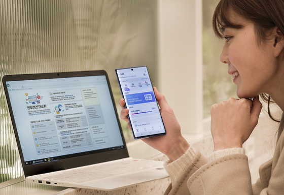 A model accesses a year-end tax settlement service using the PASS certificate. Korea's three largest mobile carriers —SK Telecom, KT and LG U+ — announced Monday that customers are allowed to use their PASS certificates at Hometax, the National Tax Service's tax administration service, from Jan. 15. [YONHAP]
