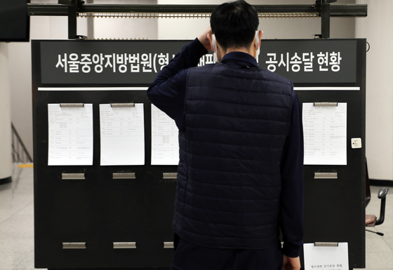 A visitor reads a bulletin board at the Seoul Central District Court in Seocho District, southern Seoul, Monday. The Supreme Court's National Court Administration earlier that day strongly recommended all court trials be delayed so as not to fall to fall between Tuesday and Jan. 11 except for urgent cases. [NEWS1]