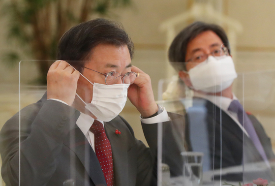 President Moon Jae-in, left, and Supreme Court Chief Justice Kim Myung-soo attend a meeting at the Blue House on Tuesday.  [YONHAP]