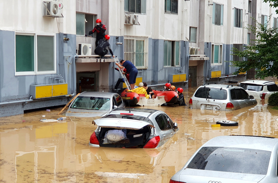 Rescue personnel evacuate residents from a flooded apartment complex in western Daejeon, which was hit by torrential rains on Thursday. [KIM SEONG-TAE]