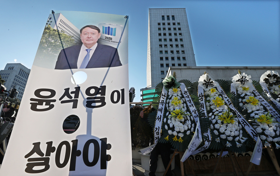 Flowers and a sign supporting Prosecutor General Yoon Seok-youl are placed outside the Supreme Prosecutors' Office on Thursday. [YONHAP]