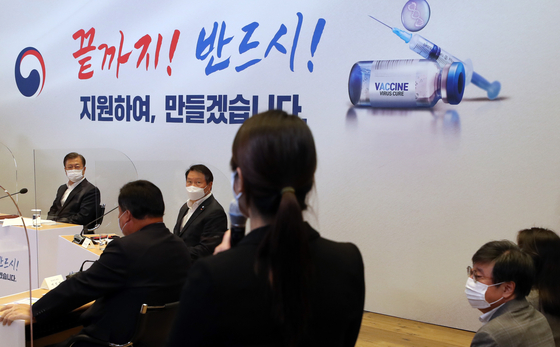 Flanked by SK Group Chairman Chey Tae-won, President Moon Jae-in, far left, listens to a researcher at SK Bioscience, a Covid-19 vaccine developer in Seongnam, Gyeonggi, about her staff's endeavor to fight the virus, on Oct. 15. [JOINT PRESS CORPS]