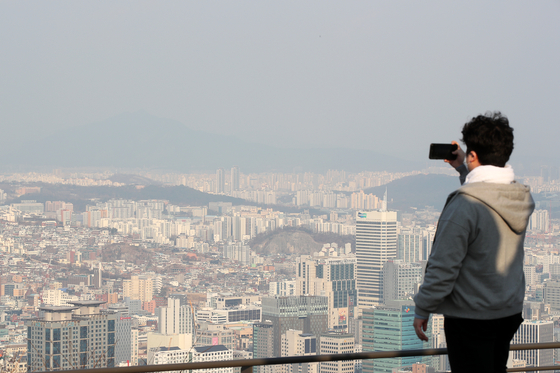 A man takes a photo of downtown Seoul from a trail on Mount Namsan on Tuesday as fine dust partially obscures the view. [JANG JIN-YOUNG]