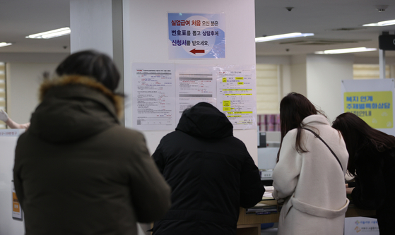 People lined up to apply for unemployment benefits, which are granted to only those that subscribed to employment insurane, at a job center in Seoul on Dec. 16. The government laid out a roadmap towards an employment insurance for all on Dec. 23. [YONHAP]