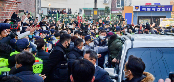Cho Doo-soon, convicted of raping an eight-year-old girl in 2008, emerges from a car amid a crowd of protestors and media to return home after being released from prison following a 12-year sentence on Saturday. [NEWS1]