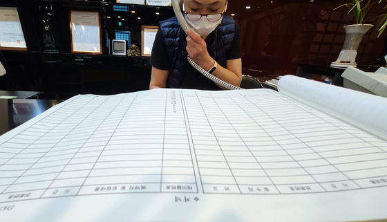 A worker at a restaurant in Jongno District, central Seoul, receives calls from customers Tuesday canceling their reservations. The reservation list is empty for the coming weeks, she said, in stark contrast to last year. [YONHAP]