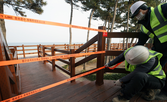 Officials in Gangneung, Gangwon, close off walking trails along Gyeongpo Beach Wednesday as the city prepares to block access to all its major tourist destinations to prevent possible transmission of the coronavirus. [YONHAP]