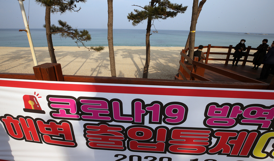 A banner says no one is allowed to enter Gyeongpo Beach in Gangneung, Gangwon, amid the concerns over the coronavirus pandemic. With the resurgence of the virus, Gangneung officials said they would block access to eight of its most popular sites for watching the Jan. 1 sunrise, including the beaches of Gyeongpo, Jumunjin, Jeongdongjin and Sacheon. The city urged the public not to visit during the holidays. [YONHAP]