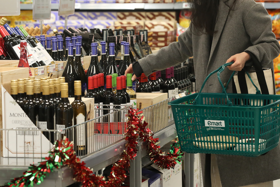 A consumer picks out wine at a supermarket in Seoul on Wednesday for the upcoming Christmas season. Retailers in Korea are scrambling to offer a mix of party products including wine, meal kits and decorations as consumers are expected to stay indoors for the holiday season due to the ongoing coronavirus pandemic. [YONHAP]