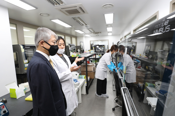 Minister of Science and ICT Choi Ki-young listens to a researcher at Seegene, a local biotech company that makes coronavirus test kits, in Songpa District, southern Seoul, in February. [NEWS 1]