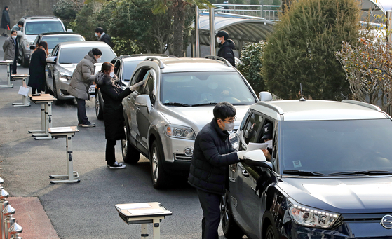 At Yongin High School in Busan on Wednesday, teachers hand out College Scholastic Ability Test scores to students in passenger cars to abide by stricter social distancing measures.  [SONG BONG-GEUN]