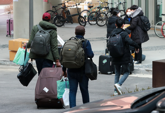 Students at the University of Seoul in Dongdaemun District, central Seoul, move out of their dormitory Tuesday to transfer to a hotel after the Seoul Metropolitan Government announced that some buildings on the school campus would be converted into so-called life treatment centers for Covid-19 patients with mild or no symptoms. [NEWS1]
