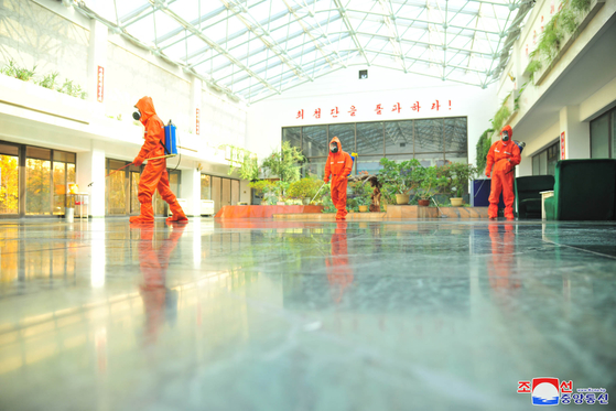 Health workers disinfect a government-run technology institute in Pyongyang on Dec. 16, in this photograph from North Korean state media. [YONHAP]
