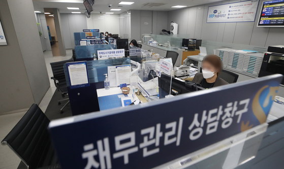 A Shinhan Bank employee works at a branch in Seoul on Wednesday. According to the bank, it has temporarily stopped accepting most loan applications from customers amid concern about rapidly increasing household debt. It is expected that it will begin processing applications again from Jan. 4. [YONHAP]