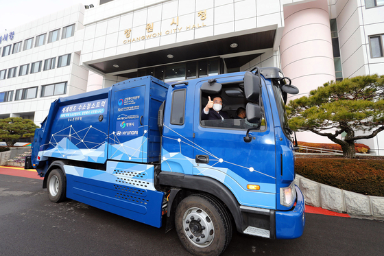 Mayor of Changwon City Huh Sung-moo rides a hydrogen-powered garbage truck in front of Changwon City Hall in Changwon, South Gyeongsang, on Monday. The city is testing the five-ton hydrogen truck developed by the Korea Automotive Technology Institute and Hyundai Motor. [CHANGWON CITY HALL]