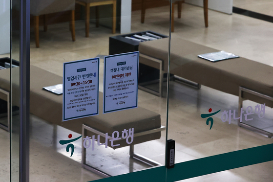 Flyers explaining a change in operation hours and a limit on the number of customers allowed in the waiting area are posted on the doors of Hana Bank's headquarters in Myeong-dong, central Seoul, on Monday. The Korea Federation of Banks announced its recommendation to limit the number of customers and clearly mark a 2 meter (6 foot) distance between customers as its version of strengthened social distancing measures for banks. [YONHAP]