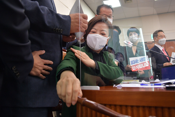 Chairwoman Jin Sun-mee of the Land, Infrastructure and Transport Committee, also a ruling Democratic Party lawmaker, is surrounded by opposition People Power Party lawmakers attempting to block the committee from passing a favorable confirmation hearing report on Land Minister-nominee Byeon Chang-heum on Monday. [YONHAP]