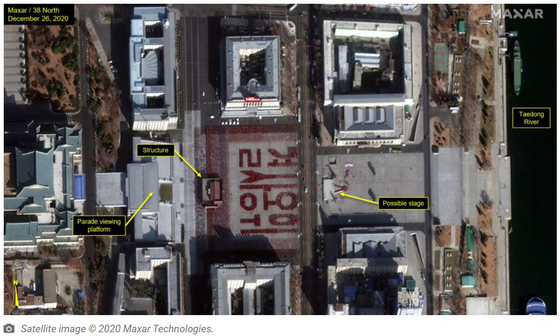 """A rehearsal is underway in Pyongyang's Kim Il Sung Square in this satellite photograph, uploaded by monitoring group 38 North. Participants hold up red placards which, in a formation, spell out a phrase that means """"defend with one's life."""" [SCREEN CAPTURE]"""